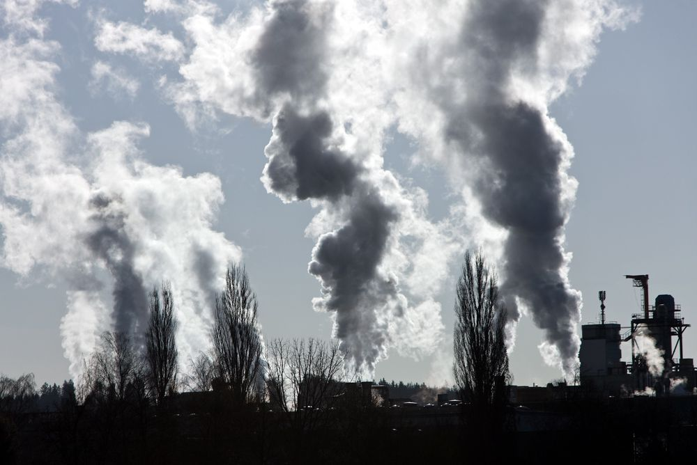 smoking chimney of an industrial company. Pollution and waste gases Klimaendringer. Global oppvarming. Illustrasjonsfoto