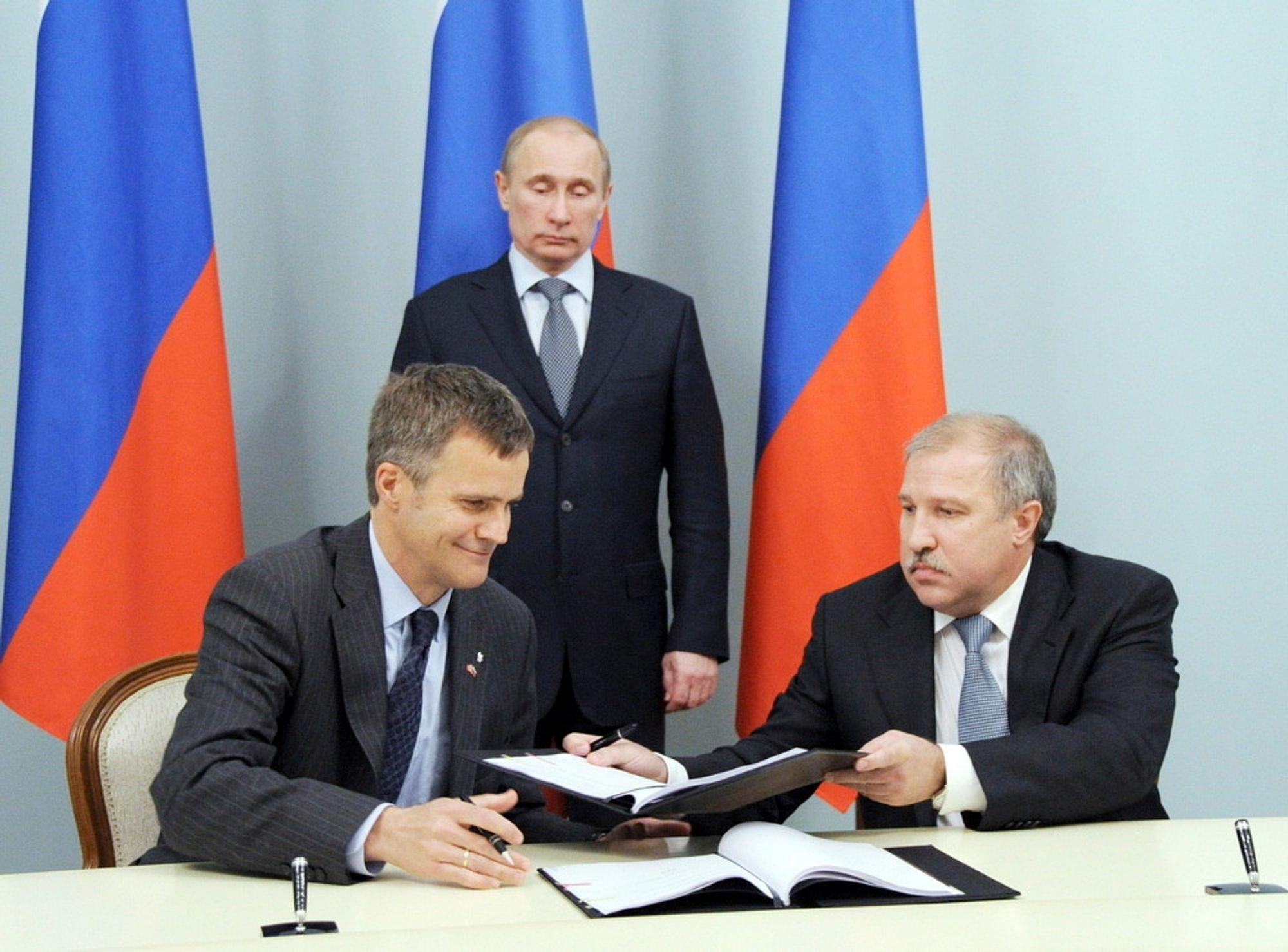 Daværende Statoil-sjef Helge Lund skriver under avtalen med Rosnefts konsernsjef Eduard Khudainatov. President Vladimir Putin iakttar begivenheten.
