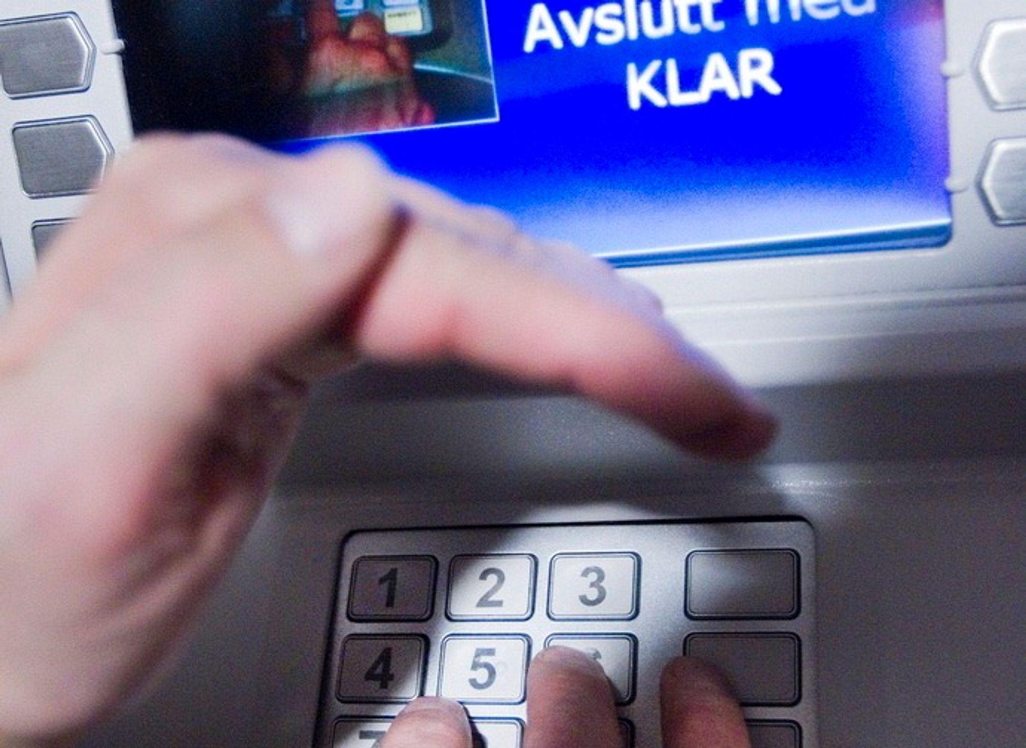 OSLO  20101027. Illustrasjonsbilde av tilfeldig minibank i forbindelse med at de i det siste har vært utsatt for skimming. Bankkunde tar ut penger, holder hånden over tastaturet når pinkoden skrives inn.  Foto: Gorm Kallestad / Scanpix .
