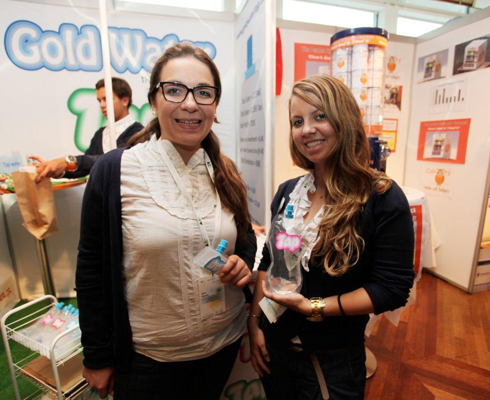 Ana Arbue, daglig leder i Gold Water, viser frem selskapets vannflaske når den er brettet sammen. Hennes kollega viser Gold Water flaske med vann i.