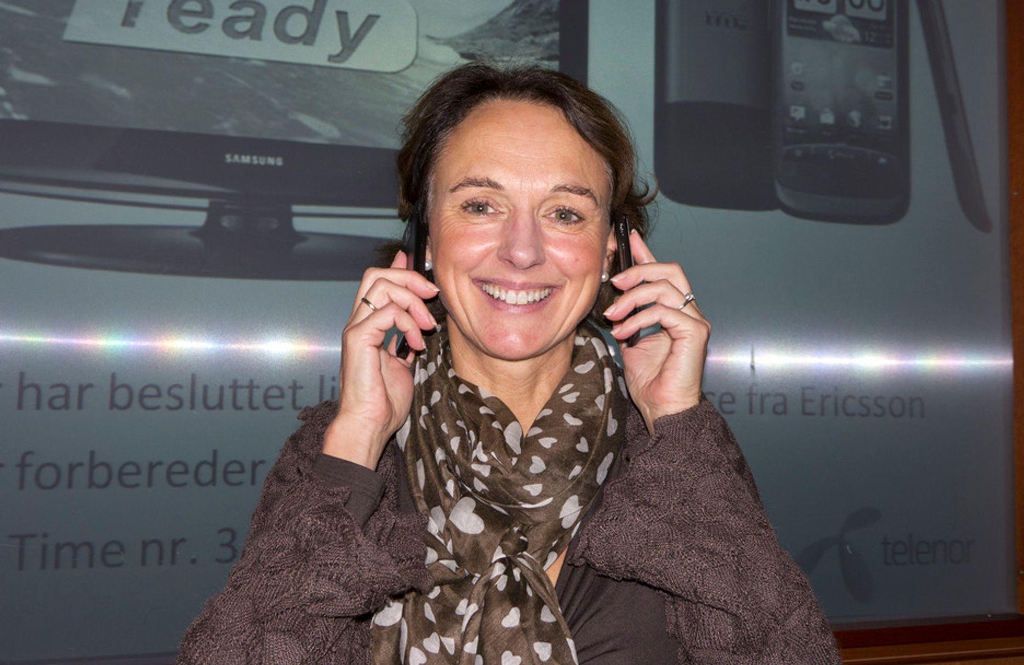 """BREDT SMIL: Direktør for stemmetjenester Birgit Bjørnsen i Telenor Norge demonstrerer """"før-og-nå- telefoni"""". En telefon med koding av et bredt frekvensområde og en med dagens smale område."""