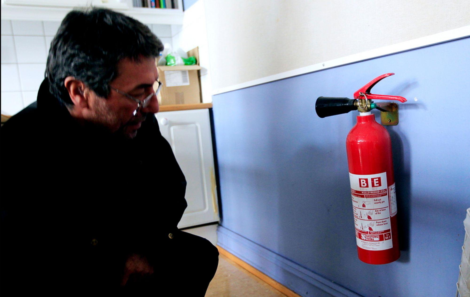 Vaktmester ved Møllergata skole i Oslo står ved et CO2-apparat av typen som forårsaket evakuering av alle Oslo-skolene torsdag. Skolen har denne typen brannslokningsapparat på spesialrom som skolekjøkken og sløydsal.