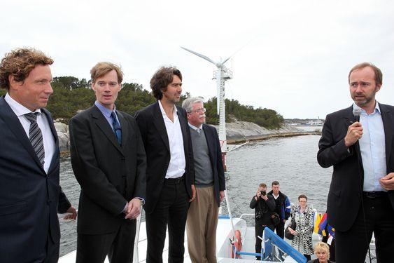 Daglig leder i Sway, Michal Forland (f.v.), oppfinneren Eystein Borgen og Jon Erik Borgen fra Inocean lytter til Trond Giskes åpningstale - med Sway-turbinen i bakgrunnen.