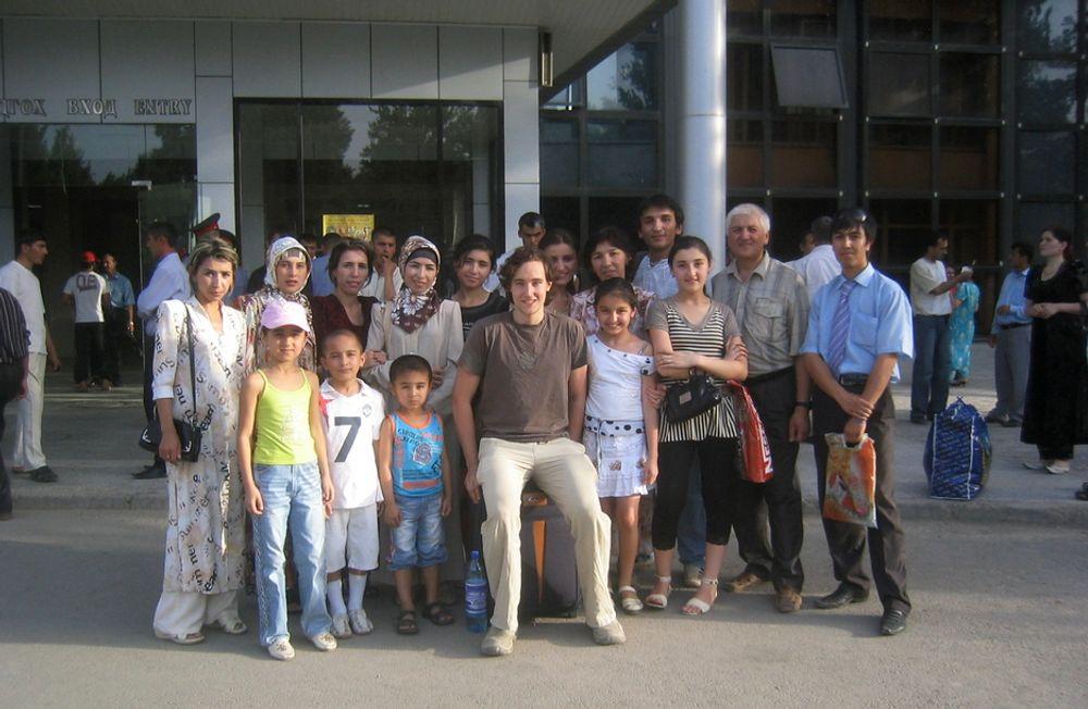 STORFAMILIE: Jon Martinsen Strand på flyplassen i Tadjikistan. Vertskapsfamilien er med og følger han til flyet til Norge.