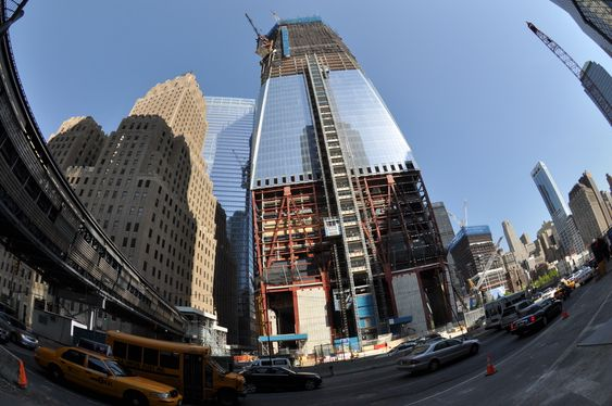 1WTC sett fra inngangen til World Financial Center i West Street. Den mye omtalte betongbasen til 1WTC skulle egentlig dekkes med prismatisk glass, men det lot seg ikke gjøre. Bak til venstre skimtes glassfasaden til 7WTC. Til høyre ser man trærne i minneparken.