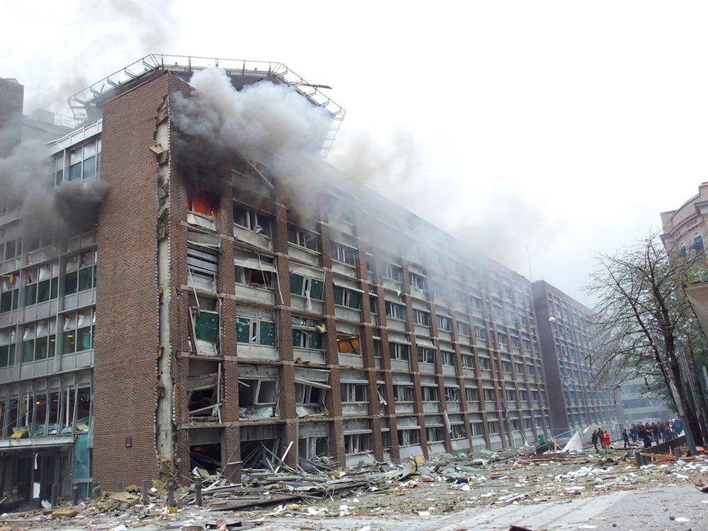 KNUST: Regjeringsbygg 4 (R4) har fått en nærmest ugjenkjennelig fasade etter eksplosjonen. Helikopterdekket på taket skimtes bak røyken fra en brann i en av de øverste etasjene.