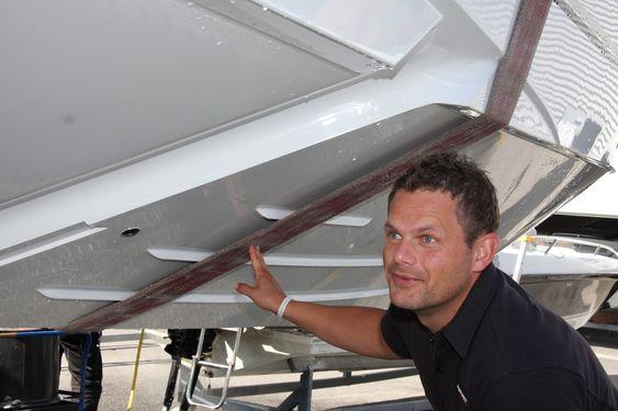 VISER:Teknisk sjef i Hydrolift, Christoffer A. Haarbye under en Hydrolift S 28 med to step. Luft føres inn under skroget via kanalene man ser tydelig nesten på tvers av skroget. Rett bak er skroget trappet ned. Ørsmå luftbobler vil dermed smøre skroget og minske friksjonen.