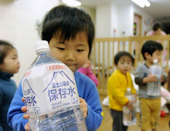 Et barn med en flaske vann i en barnehage i Tokyo. Nivået av radioaktivt jod i springvannet i byen er dobbelt så høyt som det som regnes som trygt for små barn.
