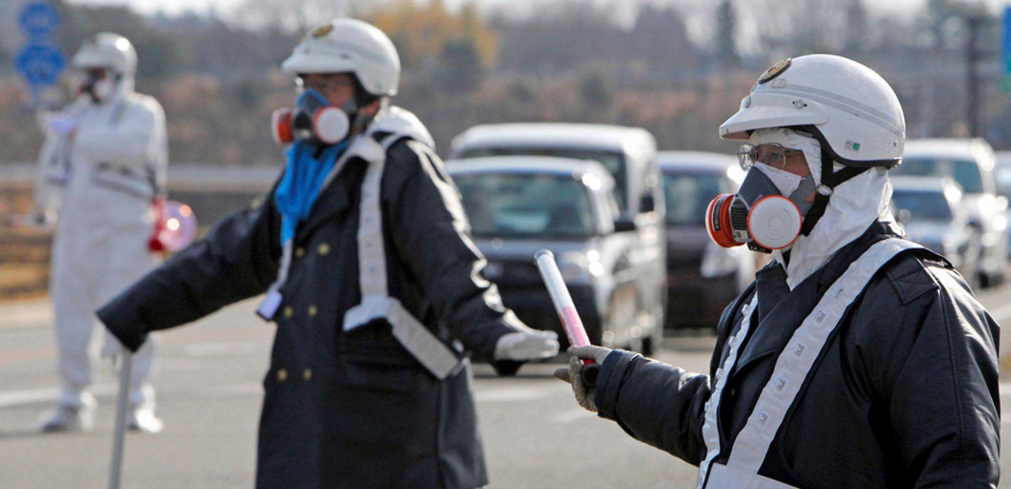 Politimenn med gassmasker leder trafikken vekk fra kjernekraftverket Fukushima Daiichi 1 under evakuering i mange kilometers radius etter radioaktive utslipp grunnet lørdagens eksplosjon ved anlegget. Nå trues tre av reaktorene av nedsmelting.