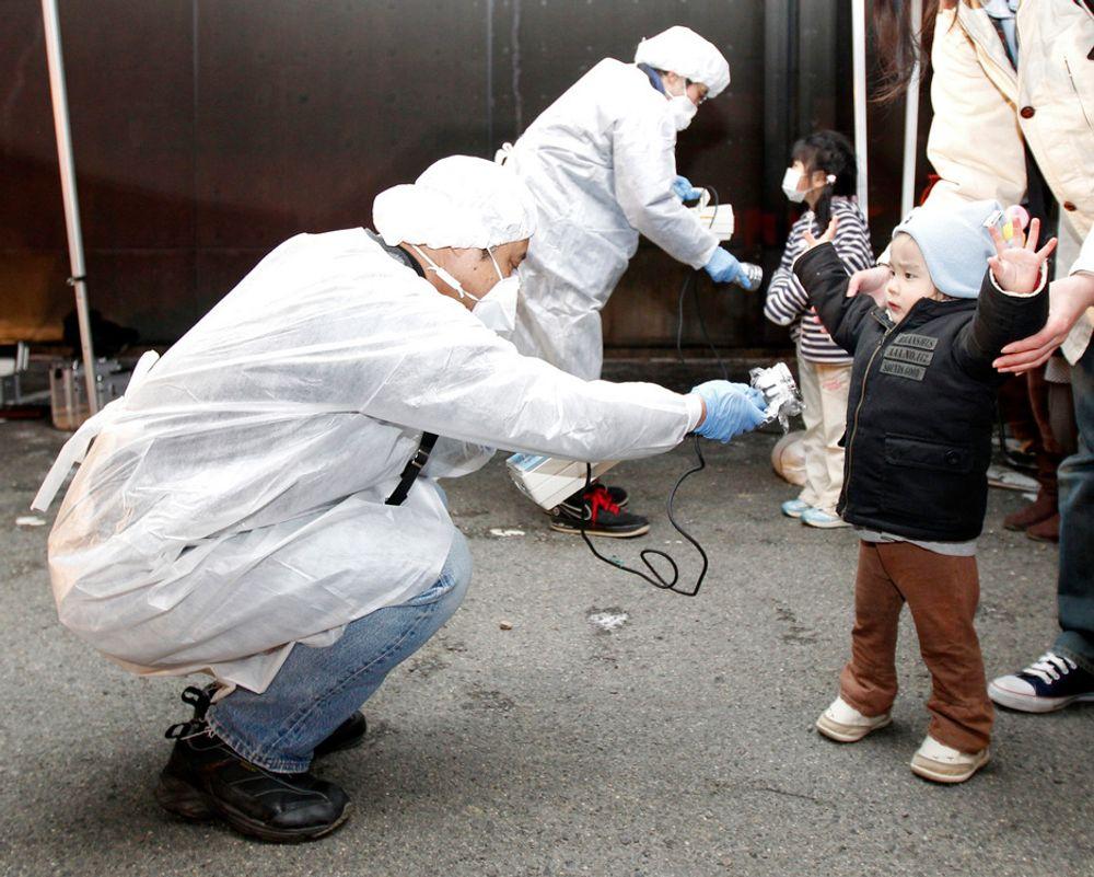 MANGLER ENERGI: Japanske tjenestemenn sjekker et barn for stråling etter evakueringen fra Fukushima-området. Nå advarer regjeringen mot kraftig energimangel. Det kan bety rasjonering hele sommeren, og en drastisk endring av livsstilen i landet.