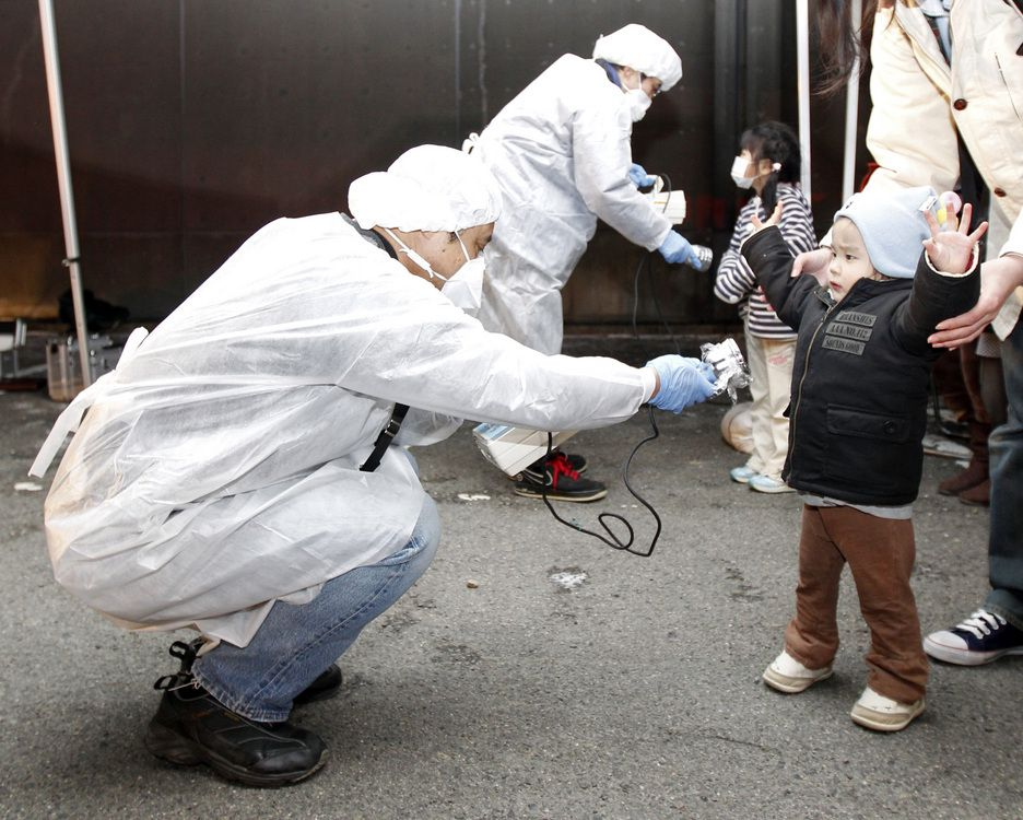 SJEKKES: Tjenestemenn i beskyttelsesutstyr leter etter spor av stråling på barn fra det evakuerte området nær kjernekraftverket Fukushima Daini i Koriyama.