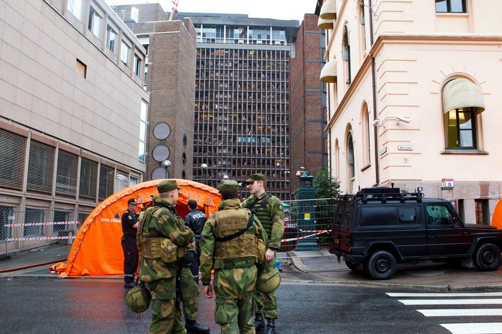 SKADET: Knuste vinduer og en ødelagt fasade. Slik så høyblokka i regjeringskvartalet ut to dager etter bomben smalt. I forgrunnen soldater med våpen og skuddsikre vester som vokter sperringene rundt åstedet.