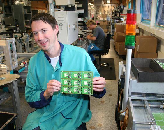 Prosjektleder Magne Nesvold i Norbitech på Røros med komponenter som brukes i autopass brikkene som lages der i fabrikken.