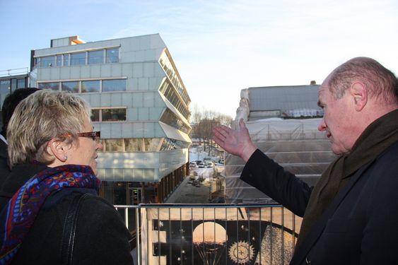 SLIK KAN DET GJØRES: Petter Groth viser kommunalminister Liv Signe Navarsete det nye energivennlige klasse A-bygget som Aspelin Ramm har vært byggherre for. På byggets sydside skrår vinduene inn, det reduserer oppvarmingen om sommeren. Undre vinduene skrår fasaden utover, der er det solfangere som bidrar til oppvarming.