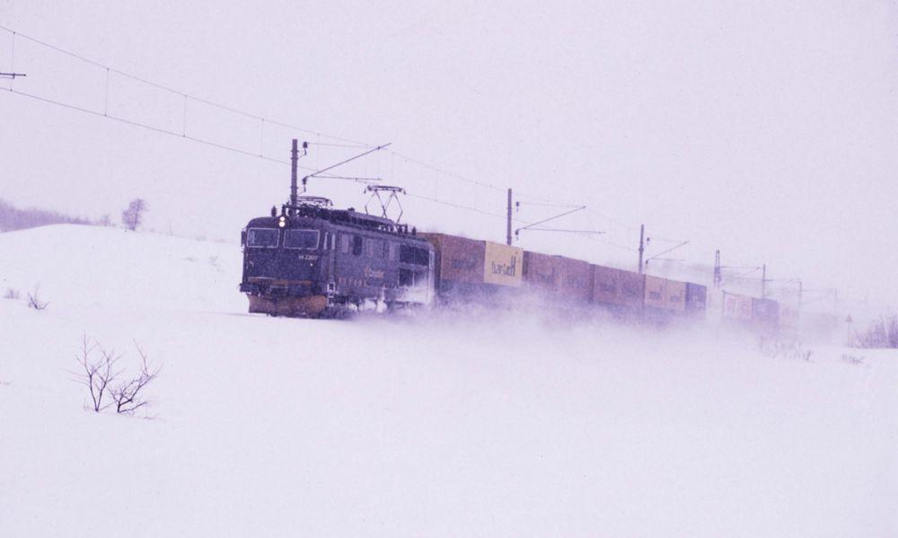 BRAGD: Da Bergensbanen sto klar i 1909, ble den internasjonalt ansett som en bragd. Senere er banen elektrifisert og tunneler og snøoverbygg er bygget om for å gi plass til moderne godstog. Her passerer CargoNets godstog Finse i fykende snøvær. FOTO: RUNE FOSSUM/JERNBANEN