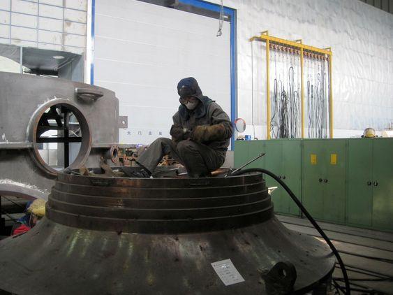 MADE IN CHINA: En kinesisk arbeider fikser på utstyret, før han dykker tilbake ned i jobben.
