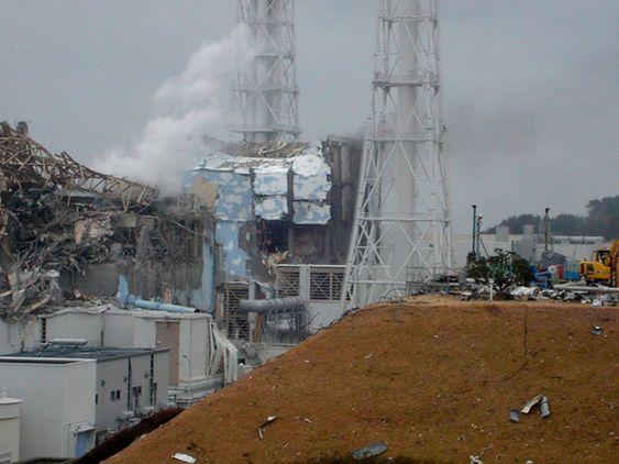 I GRUS: Reaktor 4 (i midten) og reaktor 3 (til venstre) ved Fukushima Daiichi kjernekraftverk i Japan. Bilde tatt 15. mars 2011.