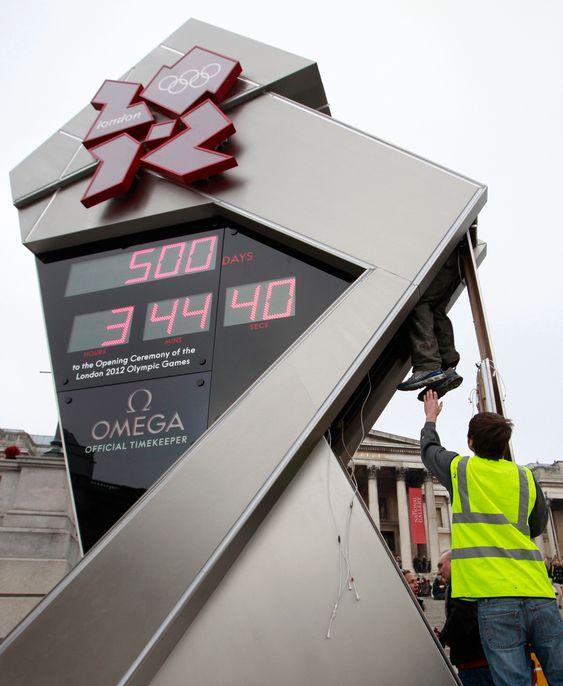 DAGEN DERPÅ: En tekniker klatrer inn i klokken som teller ned til London-OL på Trafalgar Square. Den stoppet tirsdag, bare timer etter den ble startet.