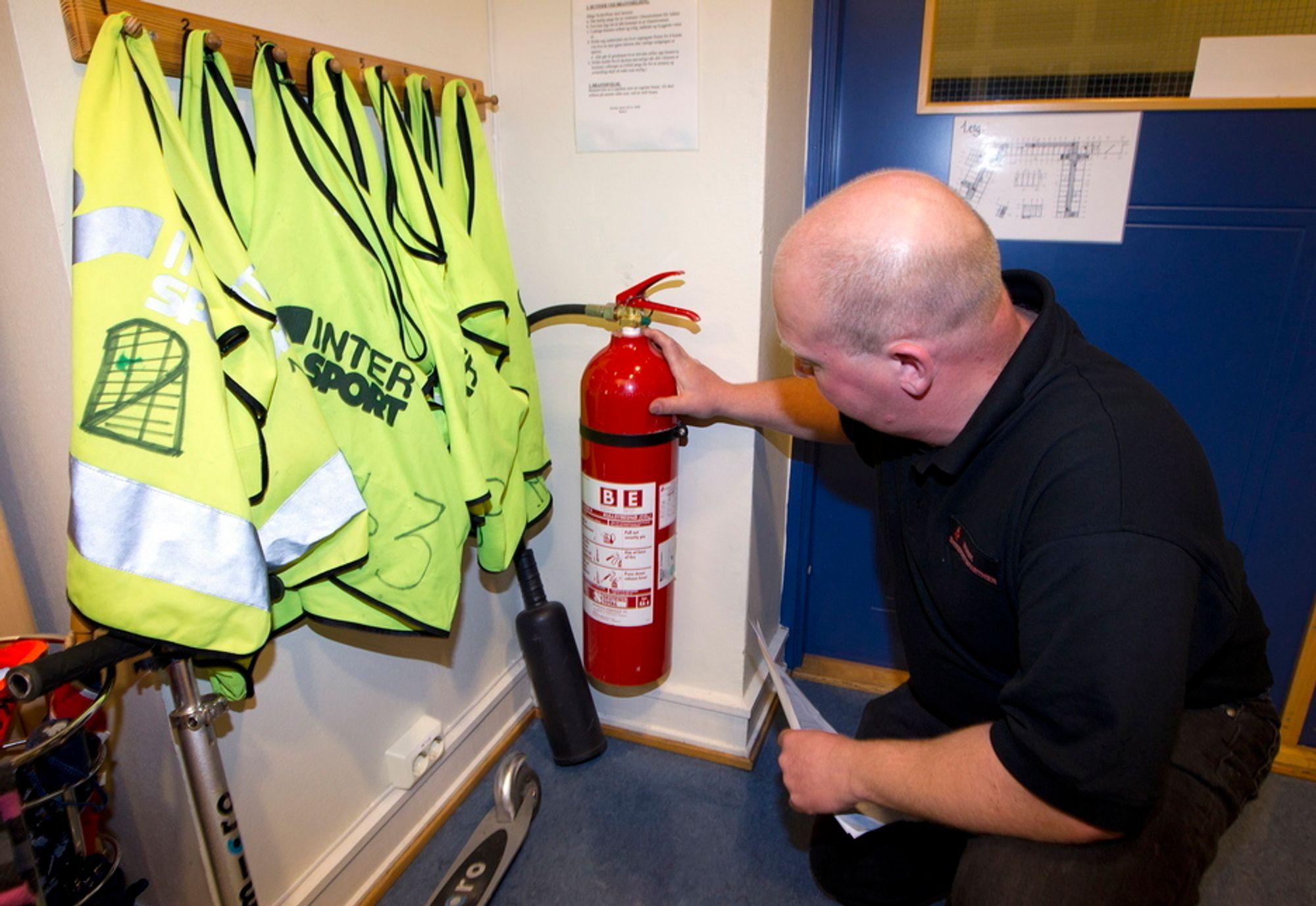 INGEN FARE: Einar Nathen i Sikkerhetspartner sjekker CO2-apparat av typen som forårsaket evakuering av alle Osloskolene torsdag. Her fra Huseby skole.