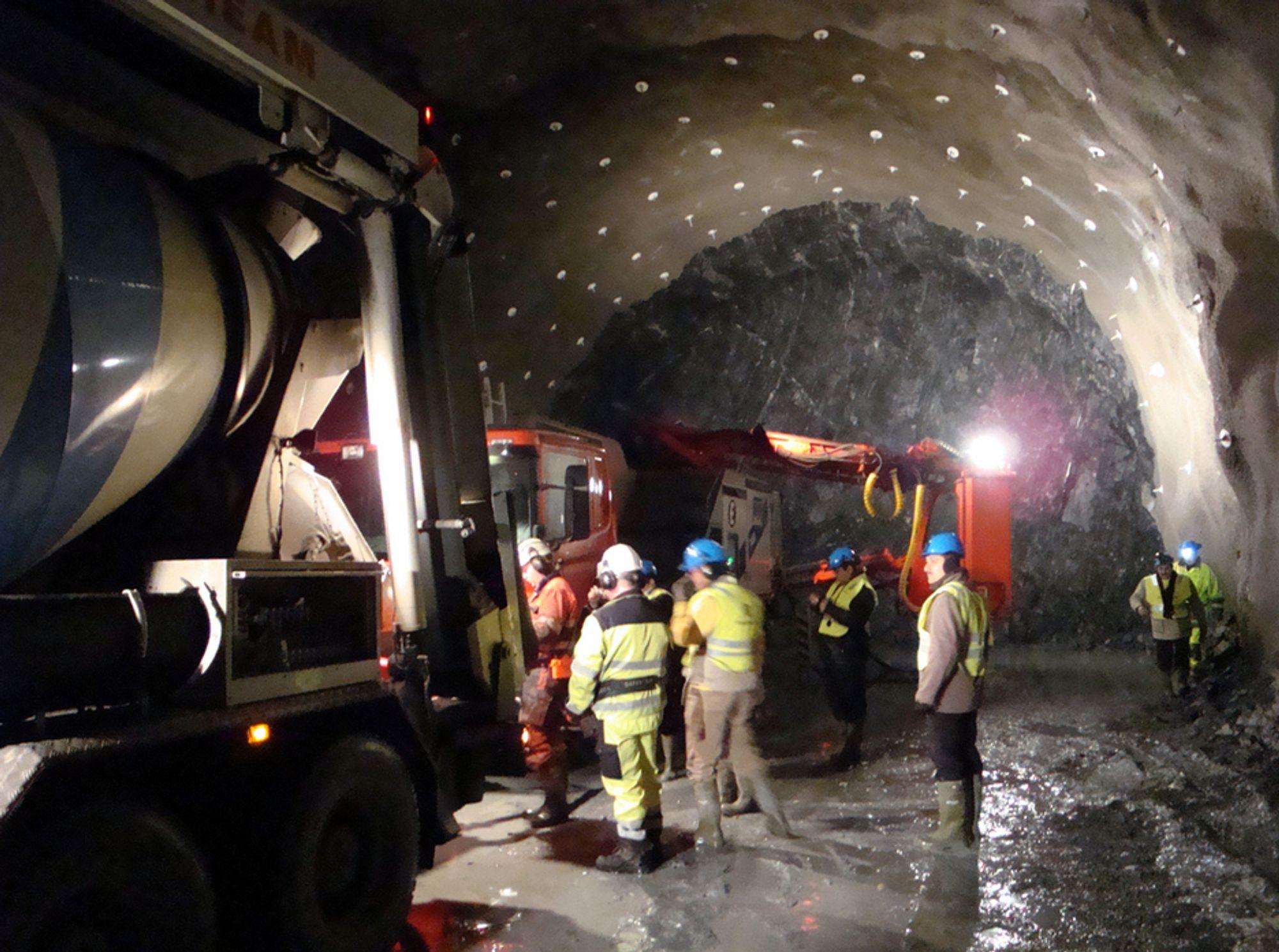 GODT EKSEMPEL: Her forbereder man for sprøyting av første lag med fiberarmert sprøytebetong S(fr) ved stuffen i Bærumstunnelen. Her brukes AMV sprøyterobot (en norskutviklet og fremragende høyteknologisk robot som er uten sidestykke i verden). Et siste lag med S(fr) for blant annet å dekke til alle boltehoder er alt som mangler av en ferdig tunnel, fordi man har løst vannproblemer med forholdsvis kostbar (i NMT-sammenheng) forinjisering. NMT ¿single-shell¿-bruk av CT-bolter og S(fr), etter forinjisering, resulterer i en tunnel som er sikrere enn Mellom-Europeiske (les sveitiske) tunneller, og mindre enn 1/5-del av prisen, tross forinjisering.