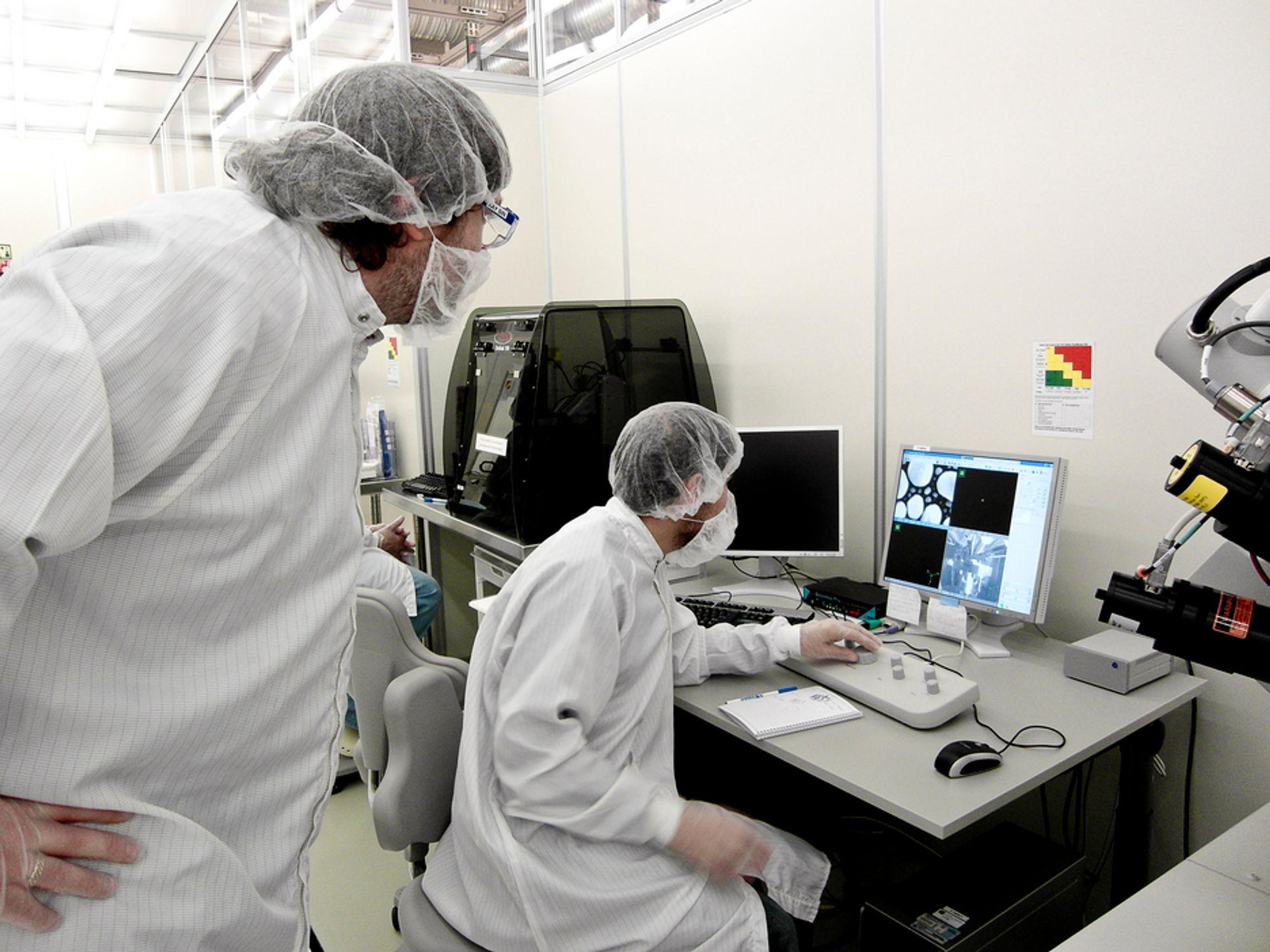 Lederen for NanoLab Kay Gastinger sammen med en doktorgradsstudent ser på  hvordan nanopartikler i gull er sett gjennom elektronmikroskopet.