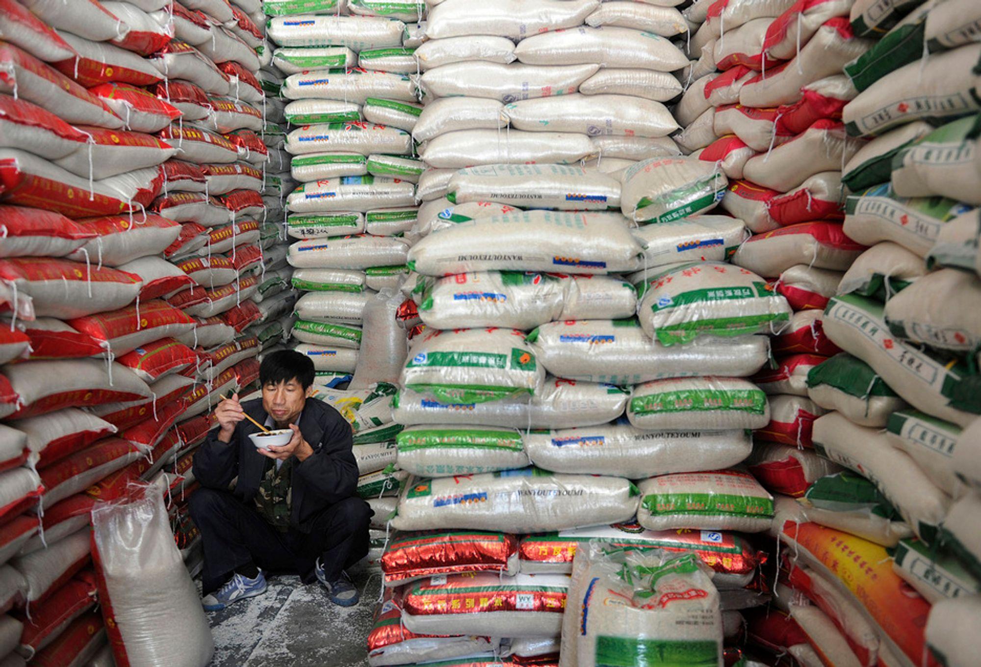 En risselger tar seg en matbit på jobben i Heifei i Anhui-provinsen øst i Kina. Rundt en tidel av rismarkene og de andre jordbruksområdene i Kina er forgiftet av farlige tungmetaller, opplyste talsmenn for regjeringen i Beijing mandag. Forurensingen skyldes blant annet utslipp fra industrien og ulovlig bruk av giftig kunstgjødsel, het det i meldinger i statlige kinesiske medier.