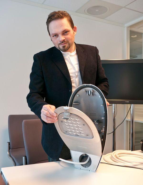 BILLIG I DRIFT: Denne LED-armaturen som ENØK-Ingeniør Christian Roger Torp holder er en 31 watt LED-lampe som erstatter en 125Watt kvikksølvdamplampe. I disse dager kommer en ny utgave av 20-watts utgave av LED-lampen med samme lysutbytte.
