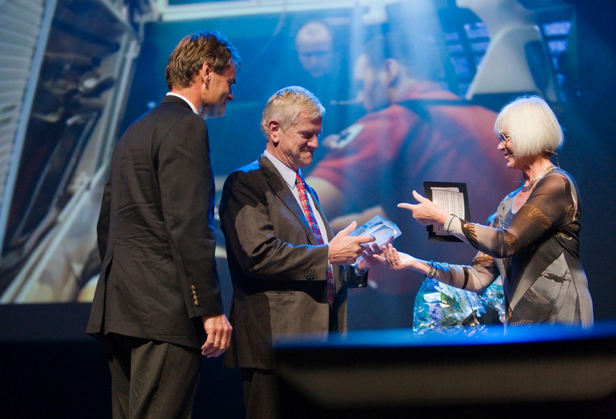 Forsknings- og høyere utdanningsminister Tora Aasland overrekker prisen til Laerdals styreleder Tore Lærdal (midten) og administrerende direktør Tor Morten Osmundsen.