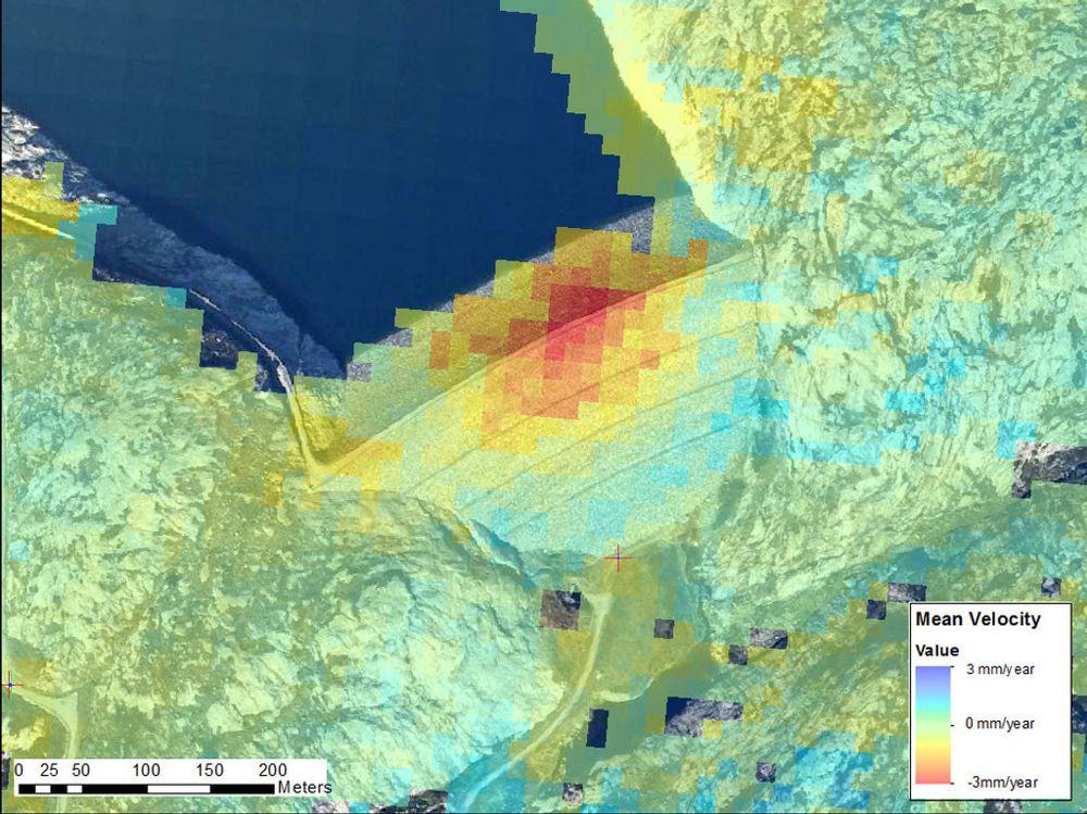 SATELLITTBILDER: Fargekodet deformasjonshastighet ved Sira-Kvinas Svartevassdammen, beregnet fra 23 radarbilder fra perioden 1992-2000. Bildene er tatt med radarinstrumenter på European Remote Sensing-satellittene (ERS-1 og 2) Det røde området langs toppen av demningen indikerer et område med setninger opptil 3 mm/år. Måleusikkerheten ved denne metoden er rundt 1 mm/år, så områder i grønt, lys gult og turkis er områder uten statistisk signifikant bevegelse. Bildene stammer fra et mindre forskningsprosjekt i samarbeid mellom Norut og NGI.