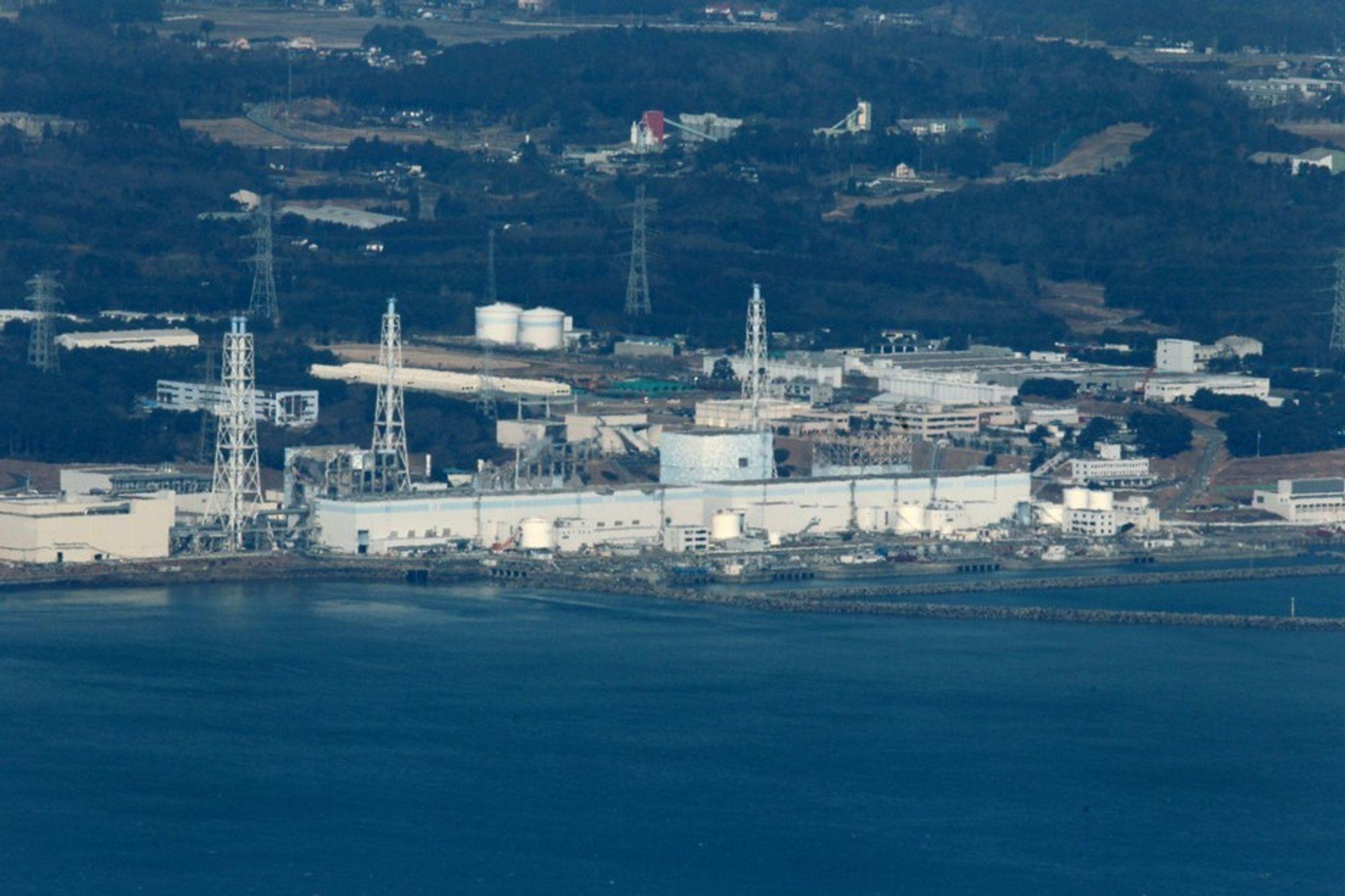 Fukushima Daiichi-kraftverket torsdag morgen. Helikoptre forsøker nå å slippe vann ned på reaktorene for å kjøle ned brenselstavene.