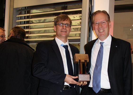 PRIS: Werner Jager (t.v.), sjef for forskning og utvikling i Hydro Building Systems, og leder for Hydros byggvirksomhet, Lars Hauk Ringvold, med prisen for beste fasadeløsning. I bakgrunnen: En TEmotion vindusmodul med integrert solavskjerming.