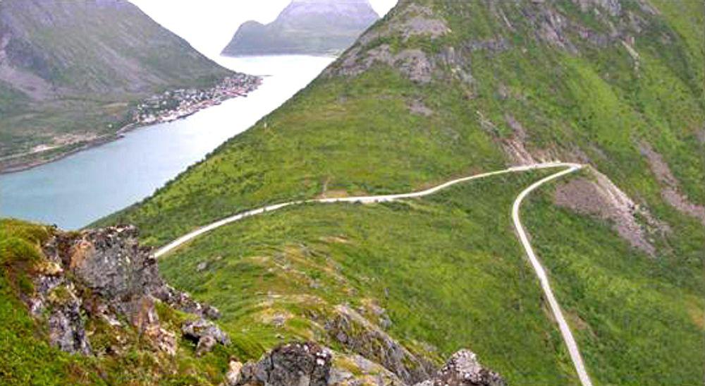 Bildet viser fylkesveg 86 over toppen av Ballesvikskaret. Fiskeværet Gryllefjord kan ses i bakgrunnen til høyre.