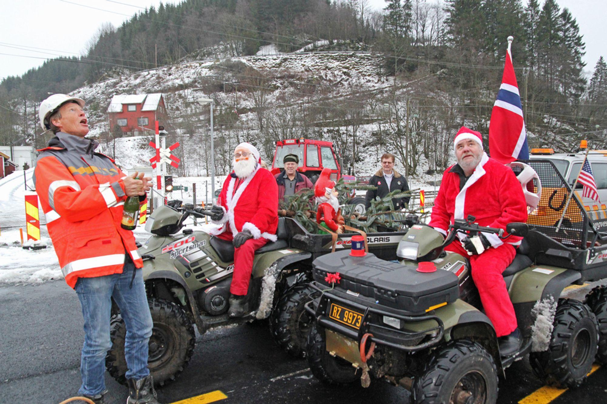 To julenisser markerte at den nye vegen mellom Helleland og Skjebadalen er ferdig. Mannen til venstre som ser langt etter korken, er prosjektleder Tor Oskar Walskaar i Statens vegvesen.