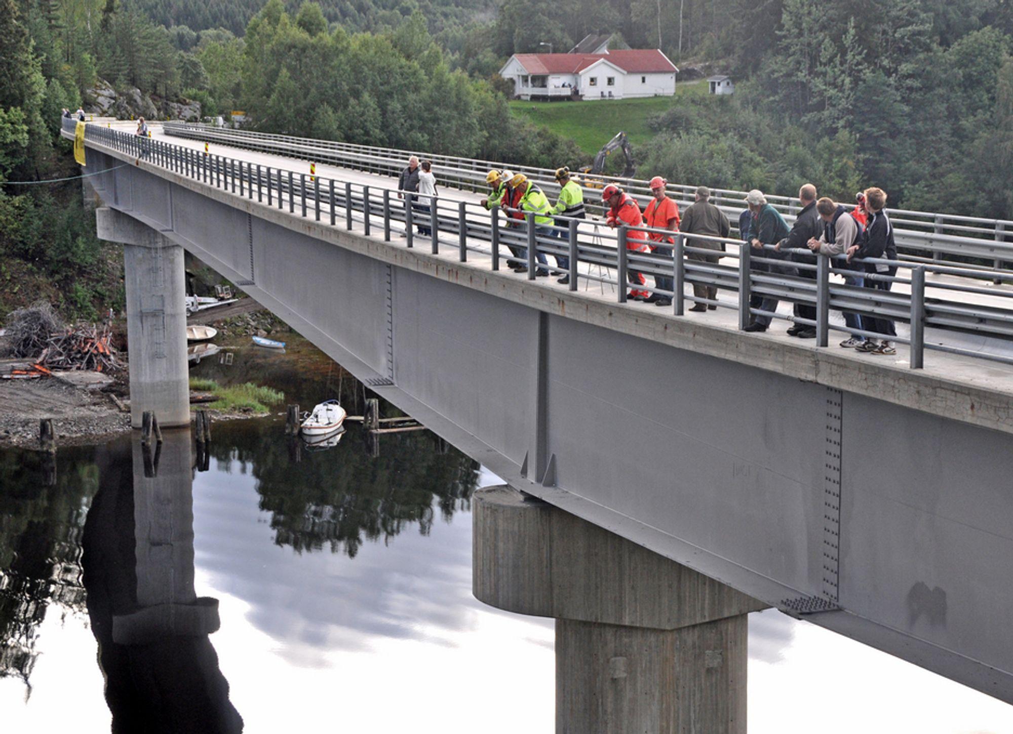 På denne siden av brua skal det monteres en gangbane. Bildet er tatt i august i fjor. De som står på brua, følger med på forberedelsene til å rive hengebrua som sto ved siden av.
