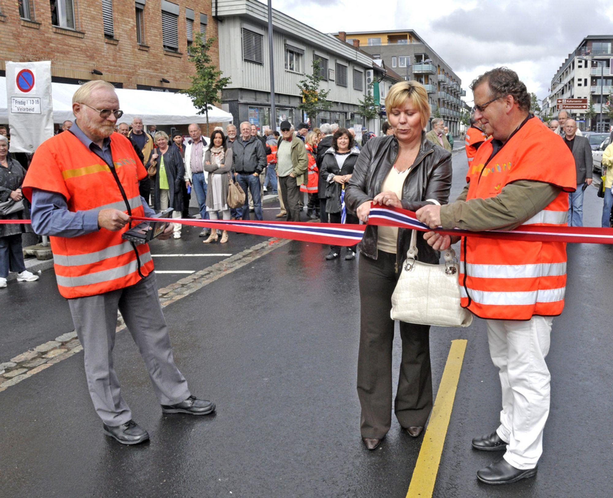 Ordføreren i Skedsmo, Anita Orlund markerer åpningen av miljøgata i Skedsmo assistert av byggeleder Tom Fjerdingby (til høyre) og avdelingsdirektør Nils-Erik Bogsrud, begge fra Statens vegvesen Region øst.