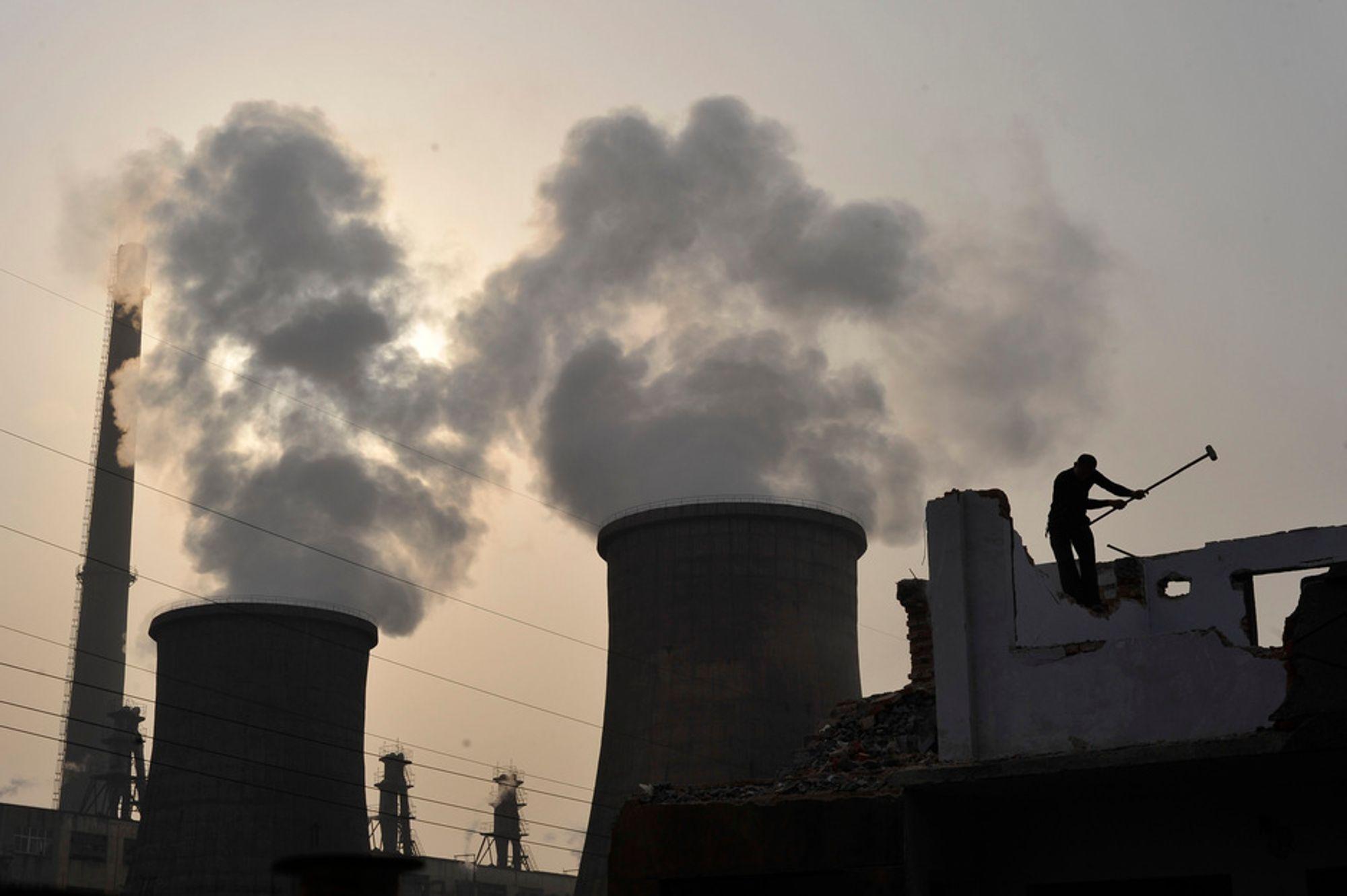 En arbeider jobber utenfor et kullkraftverk i Kina. Ingen land i verden har større utslipp av drivhusgasser enn Kina.