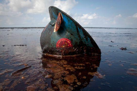 En hjelm som har tilhørt en oljearbeider, ligger og dupper i oljesølet utenfor kysten av delstaten Louisiana. Utslippet har så langt kostet BP 1,43 milliarder dollar.