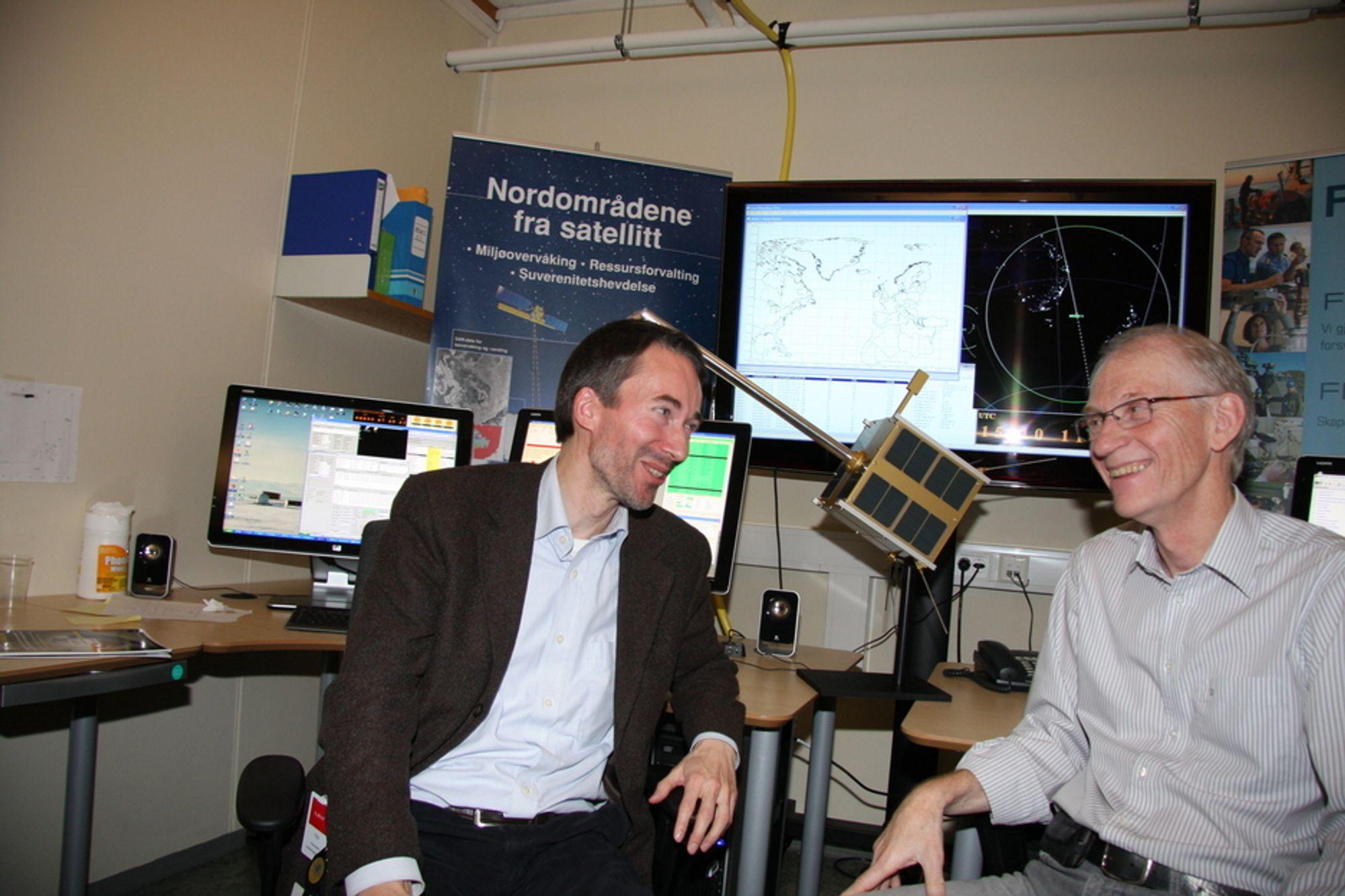 BEST: Bjørn Ottar Elseth (t.v.) fra Norsk Romsenter og Bjørn Narheim, sjefsforsker ved FFI og prosjektleder for AISsat-1, er stolte over å ha laget satellitten så lett og kompakt. Satellittkopien mellom dem er i størrelse 1:1.