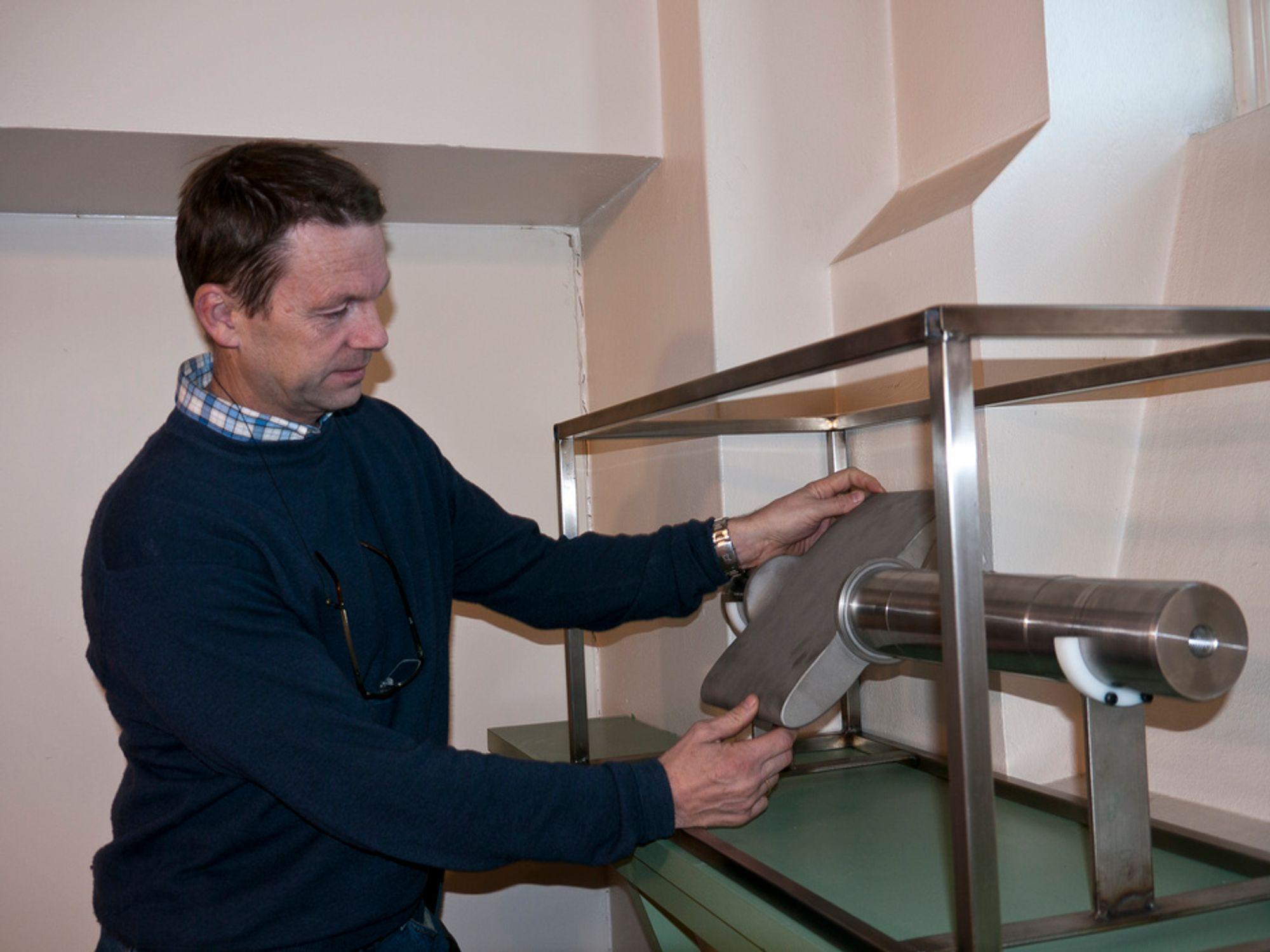 KOMPLISERT DESIGN: Professor ved Vannkraftlaboratoriet ved NTNU, Ole Gunnar Dahlhaug, viser frem en lederskovl sprøytet med Wolframkarbid til den nye sammenskrudde norske turbinen.