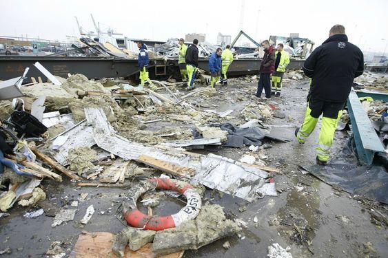 SKADER: Arbeiderne på Sjursøya betrakter skadene torsdag morgen etter at et vognsett løp løpsk og havnet i sjøen onsdag.