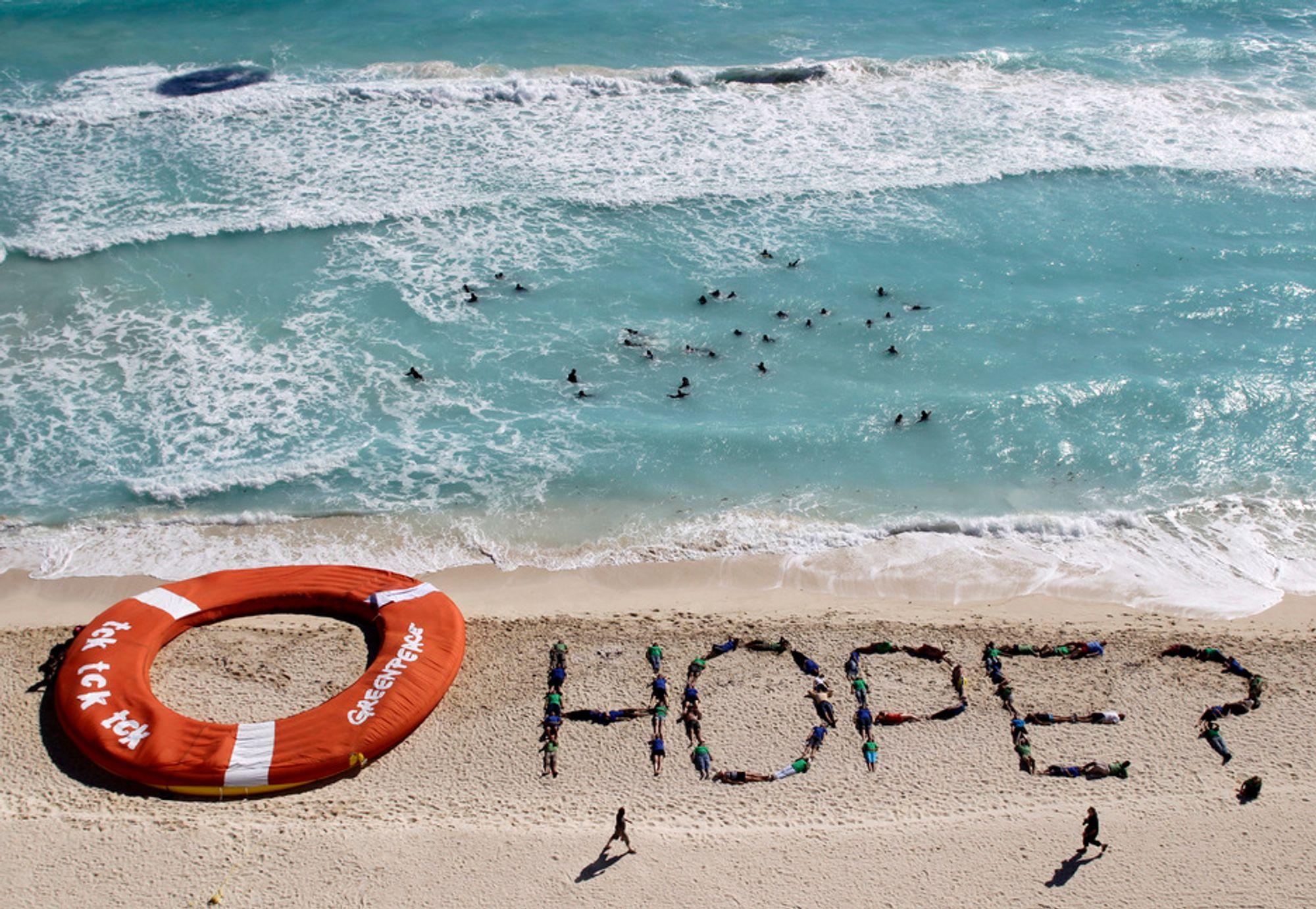 HÅP: Miljøaktivister i Cancun danner ordet «håp» på stranda. Delegatene i den mexicanske byen ble til slutt enige om en slutterklæring lørdag, og FNs klimaprosess er berget inntil videre.