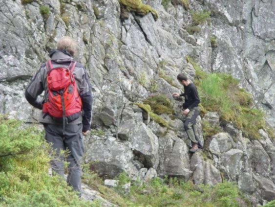 Bildet viser en student i arbeid. Med ryggen til står Henning Dypvik, professor ved institutt for geofag ved Universitetet i Oslo. Foto: Svanhild Hjorteland Gbada, Hjelmeland kommune.
