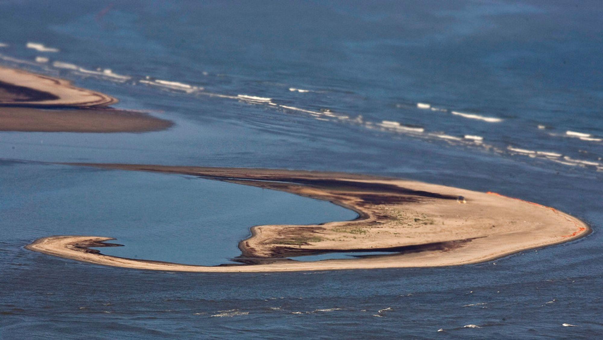 En sandbanke i South Pass i delstaten Louisiana er dekket av olje. Én måned etter eksplosjonen på oljeplattformen Deepwater Horizon lekker det fortsatt store mengder olje ut i Mexicogolfen.