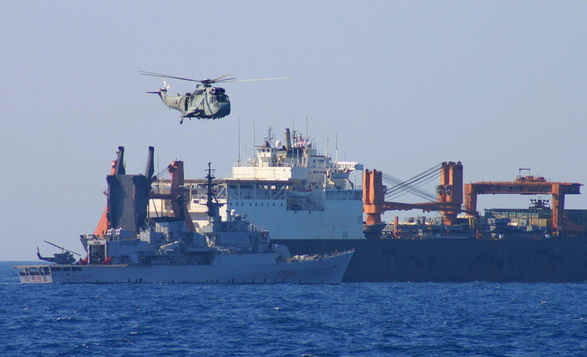 """ØVELSE: """"Kapret skip frigjøres"""". Bildet viser en italiensk fregatt og et  helikopter under en øvelse i frigjøring av et kapret skip."""