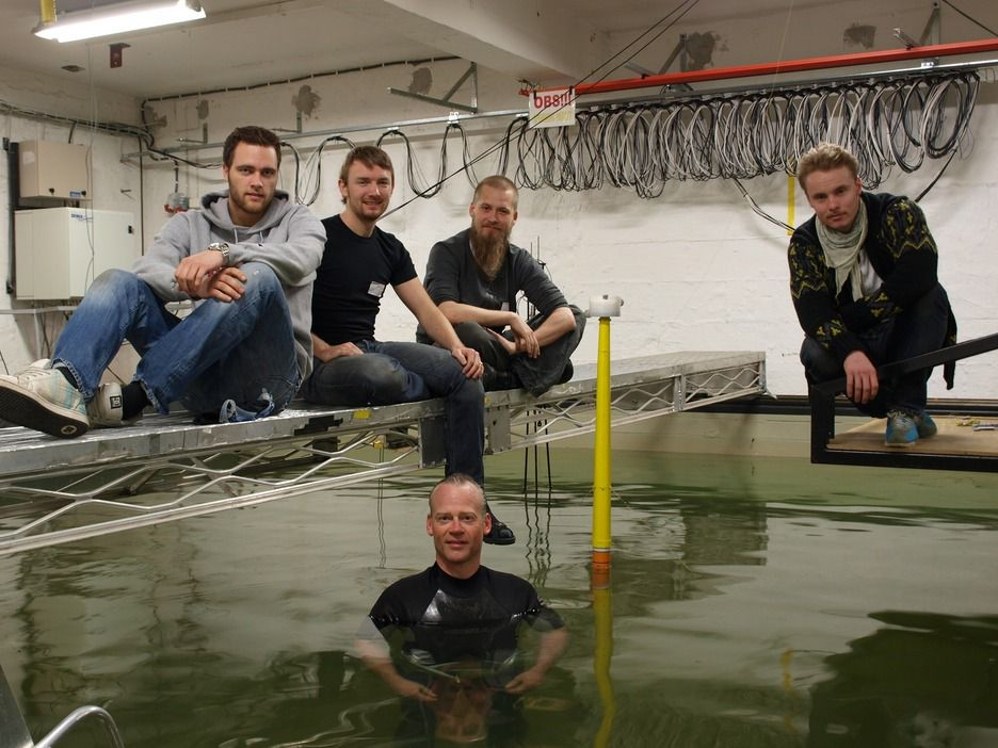 TESTES I VANNET: UMB-gruppen har testet ut den nye flytende vindturbinen i bølgebassenget til MARINTEK/SINTEF. Bak fra venstre: Fredrik Even Hansen, Anders Myhr, Karl Jacob Maus og Ulrik Aimar Møller. I vannet, ved Njord-modellen, er professor Tor Anders Nygaard.