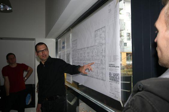 Bildetekst: Arkitekt Eckerhart Loidolt forklarer en gruppe norske arkitekter layouten til en studentbolig i Wien.