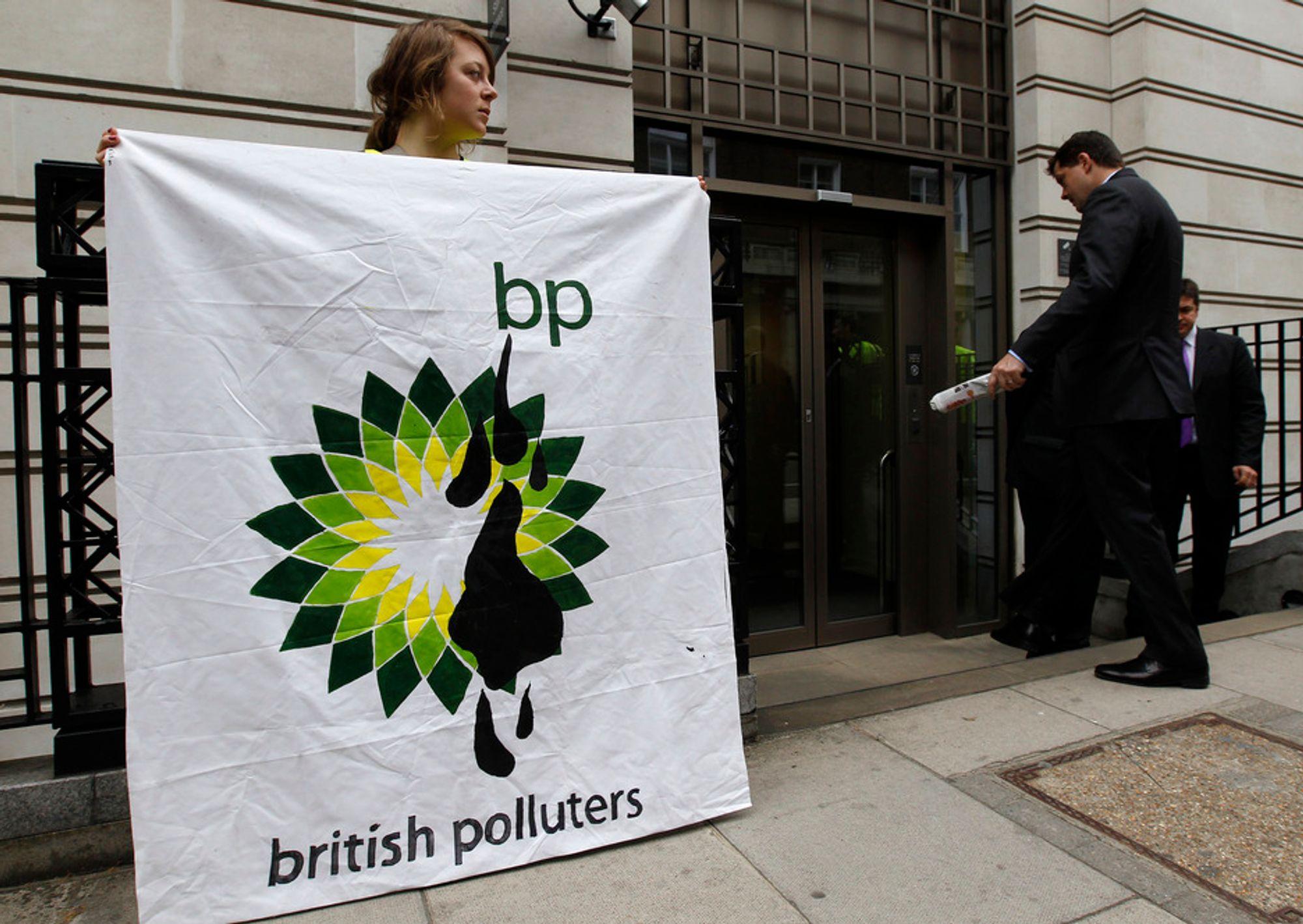 En Greenpeace-aktivist holder opp en banner foran BPs hovedkontor i London torsdag.