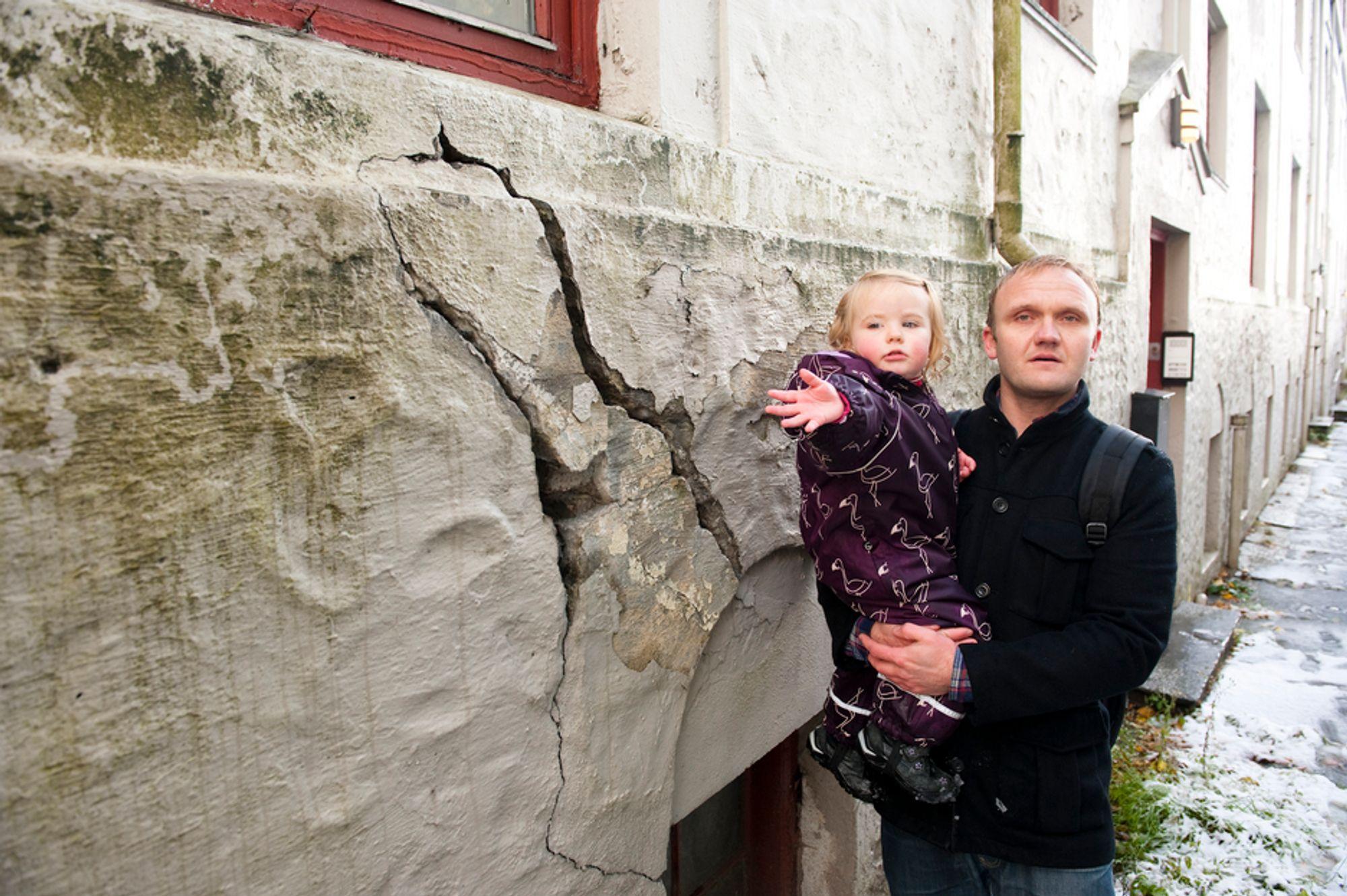 UTYGT: Heine Askeland og datteren Mia viser noen av sprekkene i muren i gården i Ladegårdsgaten i Bergen. Nærmere halvparten av beboerne er evakuert fordi bygården har fått store setningsskader og kan være farlig å bo i.