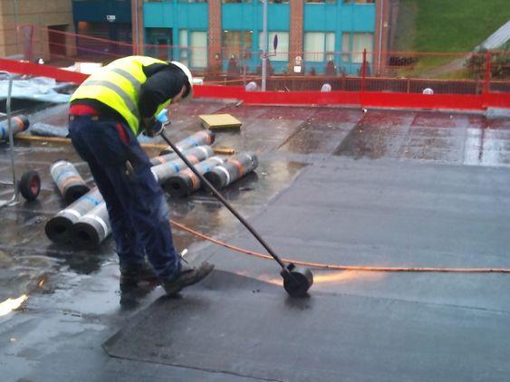 TETTER: På taket er arbeidene med å legge papp godt i gang.