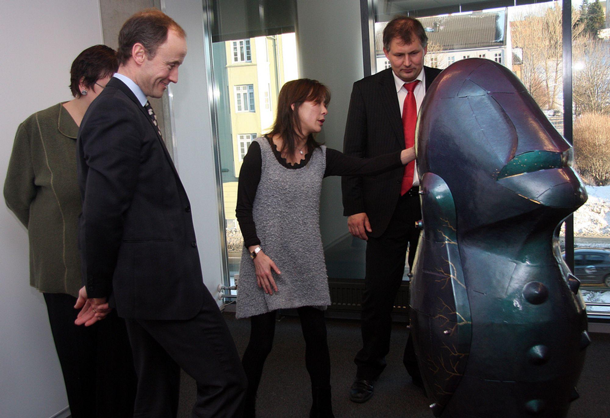 AVDUKET: Kunstner Jannicke Olsen forklarer olje- og energiminister Terje Riis-Johansen hvordan hun har forvandlet oljekjelen til et kunstverk.